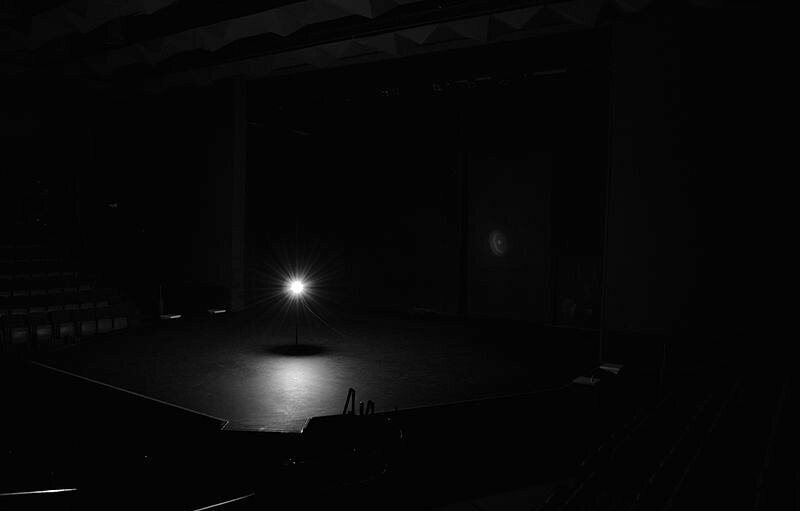 A ghost light in a darkened theatre