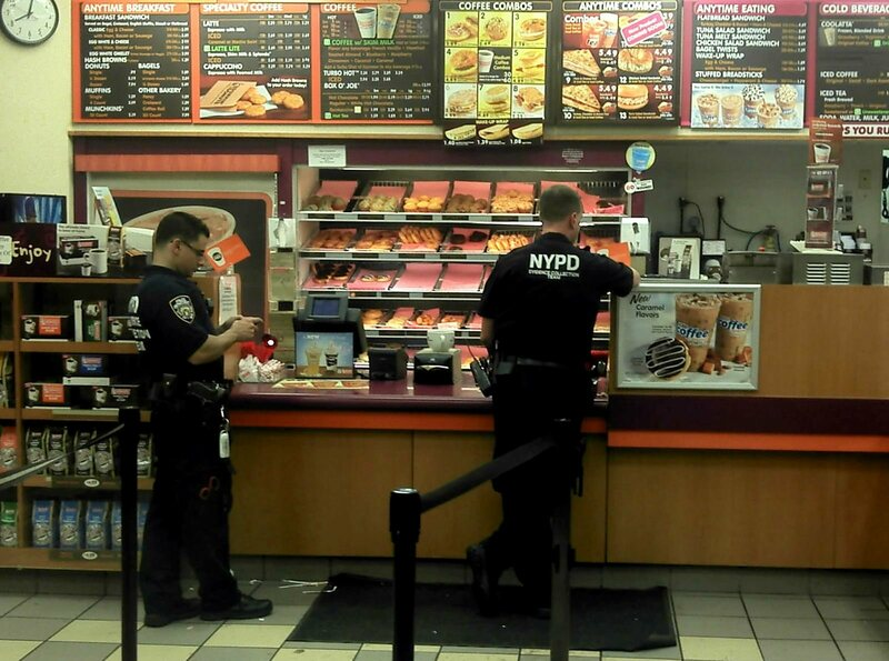 NYPD officers case an East Village Dunkin' Donuts.