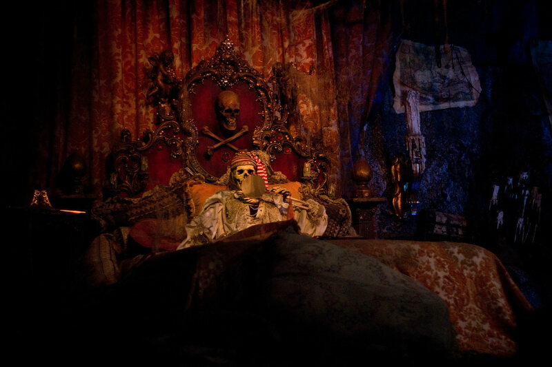 A fake skeleton, cozy in a bed decorated with an (allegedly) real skull.