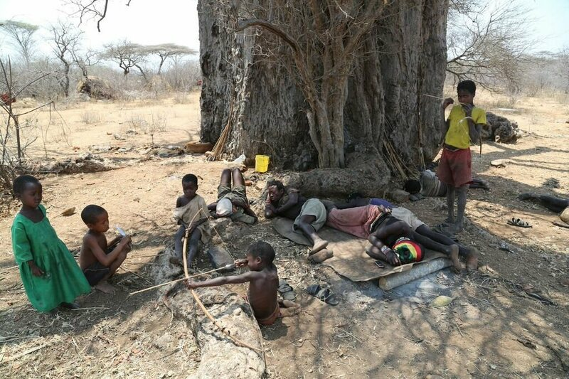 Hadza people hanging out under a tree.