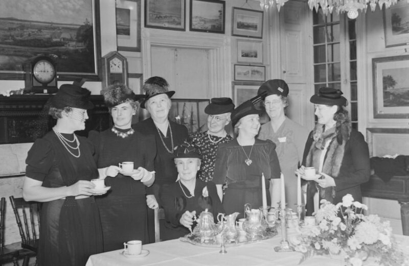 """Women's """"Catholic Women's Club"""" have tea at a table on which are silverware. In the background, we see several paintings on the wall and two antique clocks on the mantelpiece of the fireplace. 1940"""