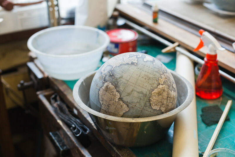 Apprentices train for at least 6 months before making the smallest sized globes, the 23cm mini desk globe. At the end of each day, their practice globes are soaked in water and stripped back so they can practice again the next day. Photo by Ana Santl.
