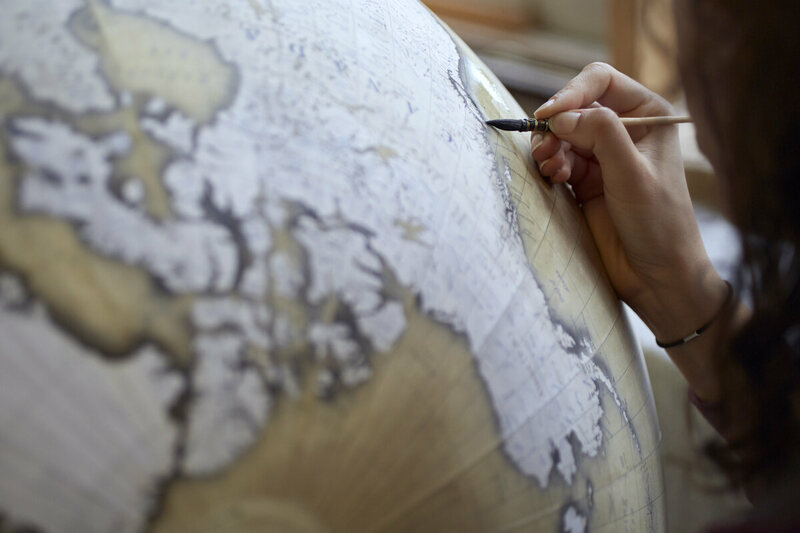 Watercolour artist Isis who has been with the company over 3 years paints the detail on the larger globes, here she is shading around the continents on an 80cm globe. Photo by Tom Bunning.