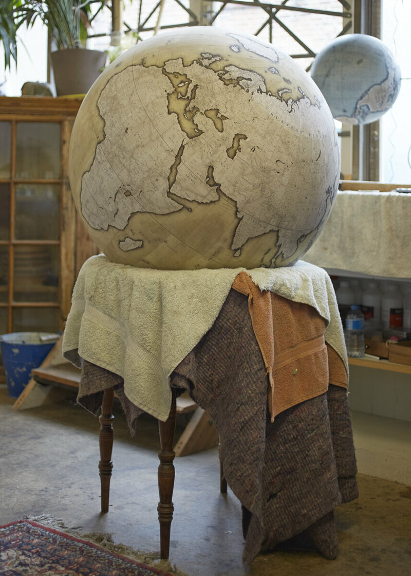 An 80cm handcrafted and hand painted globe in progress, the ocean have been painted, then the shading around the continents, now further detail will be painted in the continents along with final washes of colour because the globe is placed on a handcrafted wood or metal base and shipped off to its new home, photo by Tom Bunning.