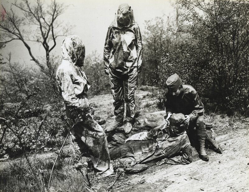 Three camoufleurs in the Women's Reserve Camouflage Corps  make one woman disappear into the forest floor.