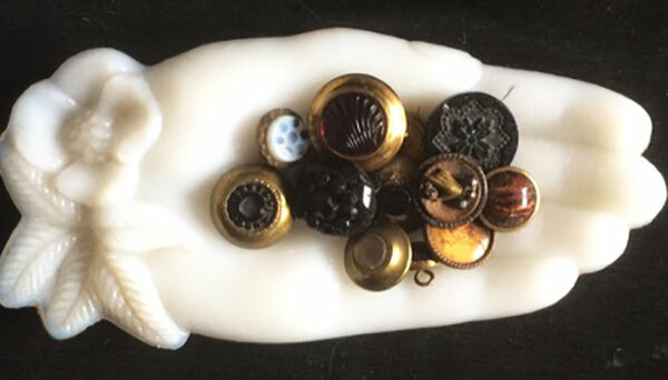 A hand-shaped tray holding buttons, one of which also features a bodiless hand.