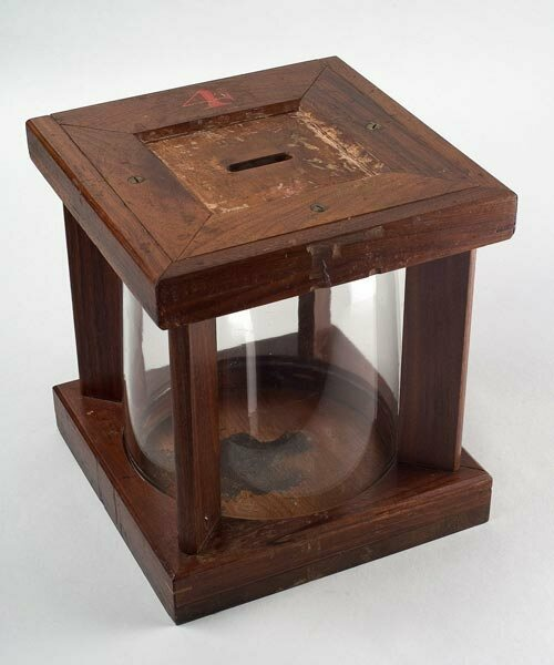 A later version of the glass ballot box with a cylindrical shape.