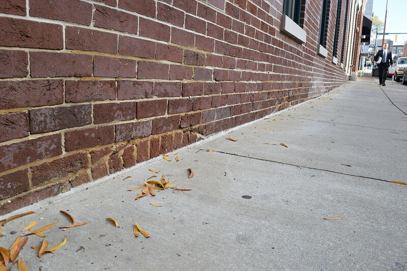 Brickwork disappears past the sidewalk along E 7th Street in Chattanooga.