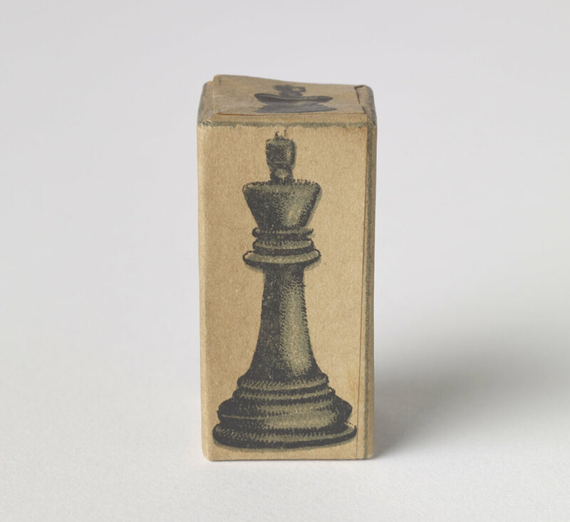 An improvised chess piece produced during the siege of Leningrad in WW2, consisting of a cardboard box printed with the shape of a Staunton Set piece.
