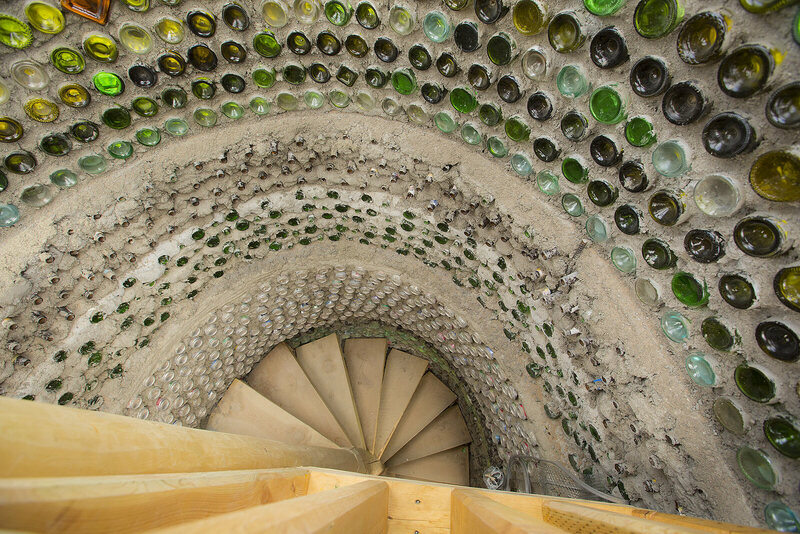 An intricate mosaic wall of bottles in a two-story Earthship.