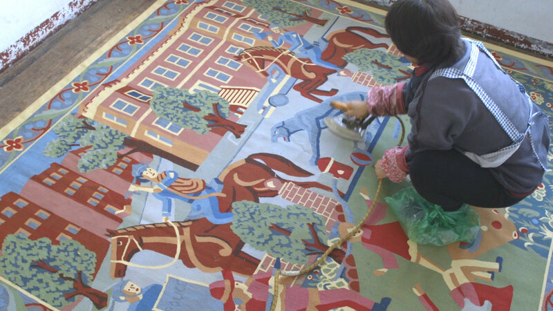 A textile artist finishes off the tapestry, which was woven at Renaissance Carpets and Tapestries in New York.