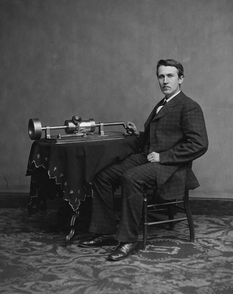Edison poses by his phonograph in a photograph from 1878.