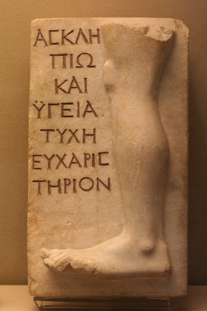 "Votive relief for the cure of a bad leg. The inscription reads ""Tyche to Asclepios and Hygieia as a thanking gift."""