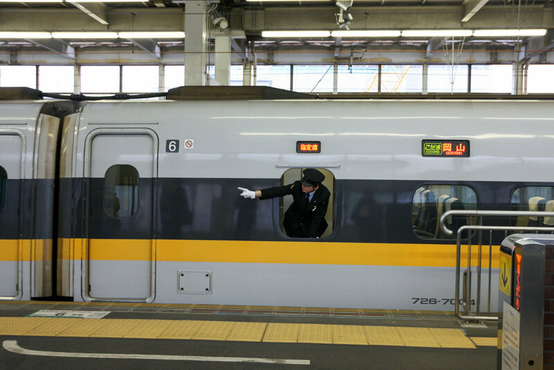 A Hiroshima train conductor pointing along the track.