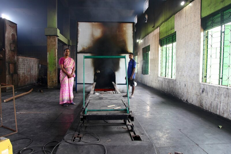 Crematorium assistant Divya Raju and a furnace operator pose in front of an active furnace.