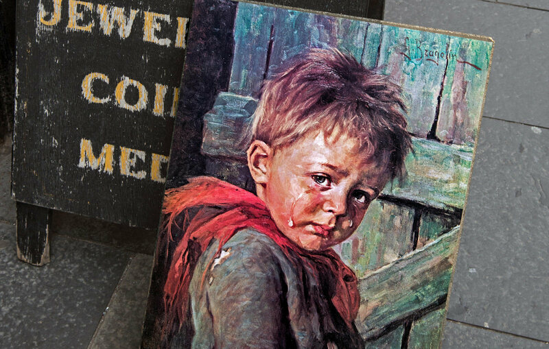 "A ""crying boy"" painting for sale outside an antiques store in Edinburgh."