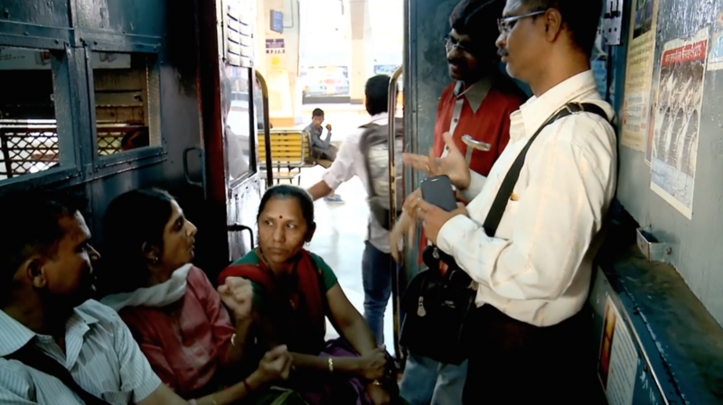 Deaf commuters converse in a Mumbai railway car.