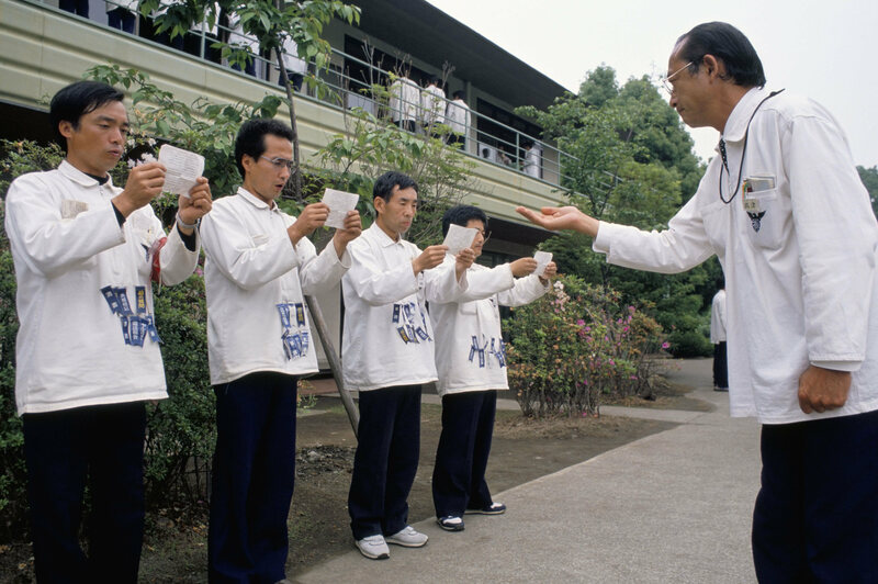 """Hell camp executives in training in Japan, wearing """"ribbons of shame."""""""