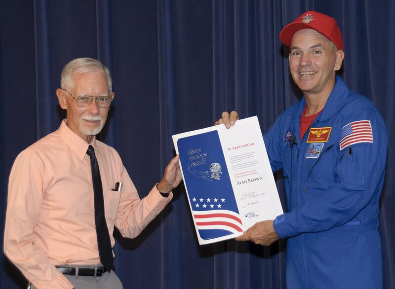 Astronaut Rick Sturckow awards the Silver Snoopy to news chief Alan Brown for his support of the Space Shuttle Program.