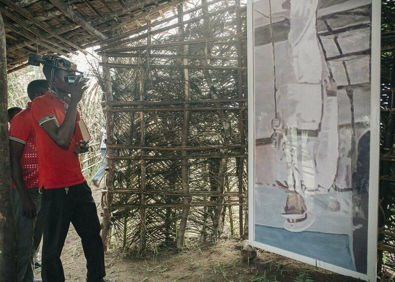 A visitor seeing Luc Tuymans' <em>Mwana Kitoko</em> through Carsten Holler's Upside Down Goggles in one of the Kisendus.