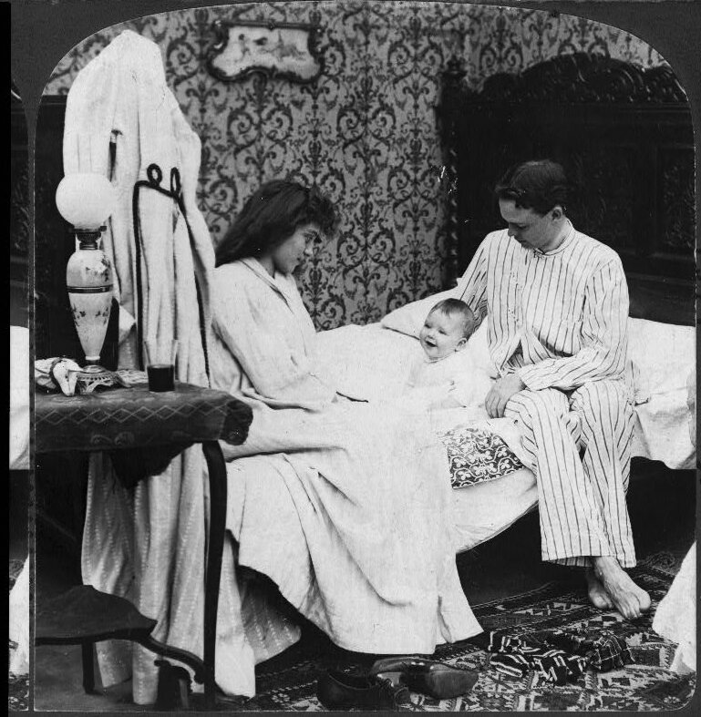 A family sitting on a bed, dressed in sleeping attire.