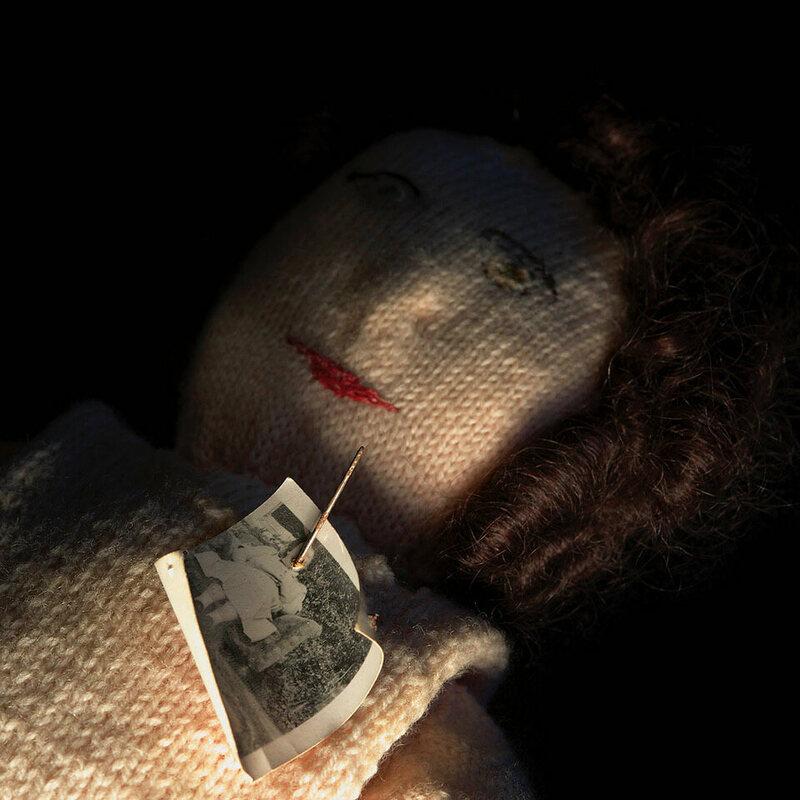 A knitted poppet with photograph, used to represent a particular person when casting spells that will affect them.
