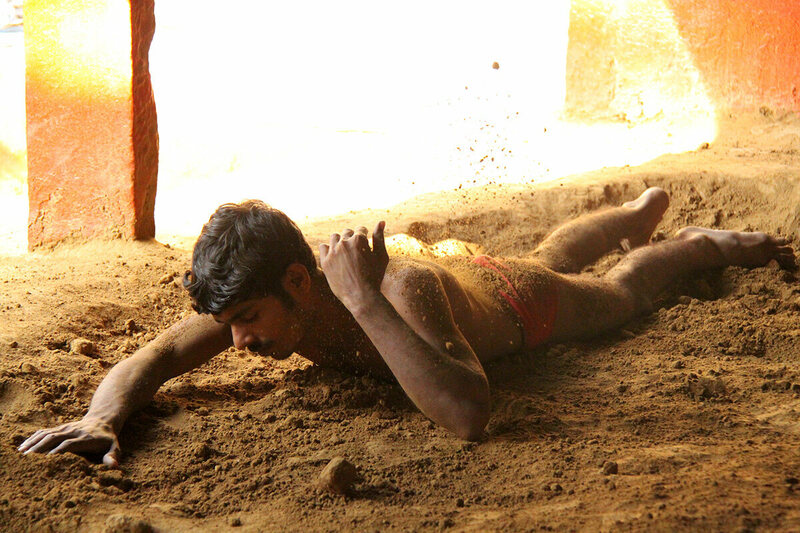 A pehlwan rubs mud over his body to create friction during wrestling sessions.