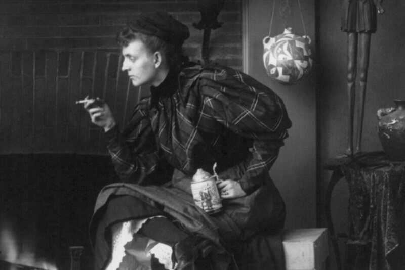 "Photographer Frances Benjamin Johnston, holding a cigarette and a beer stein, in her <em>Self Portrait (as ""New Woman"")</em>, 1896."