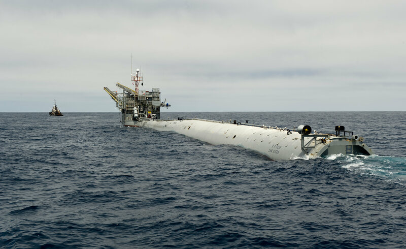 FLIP, being towed into position by a tugboat. The spar is the narrow end in the foreground.