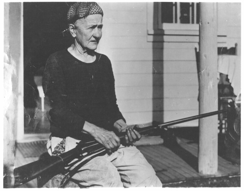Quigley on the porch of her house in Kantishna, holding a rifle, c. 1940