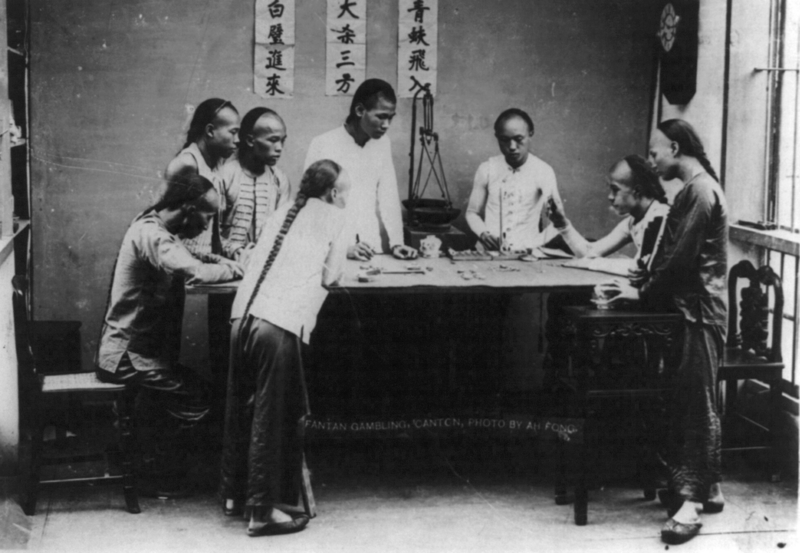 "A group of men gambling together with the traditional ""queue"" hairstyle."