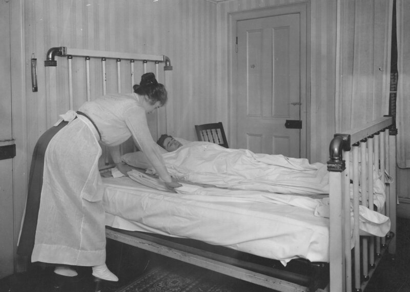 A Red Cross nurse change the sheets on a patient's bed, 1917.