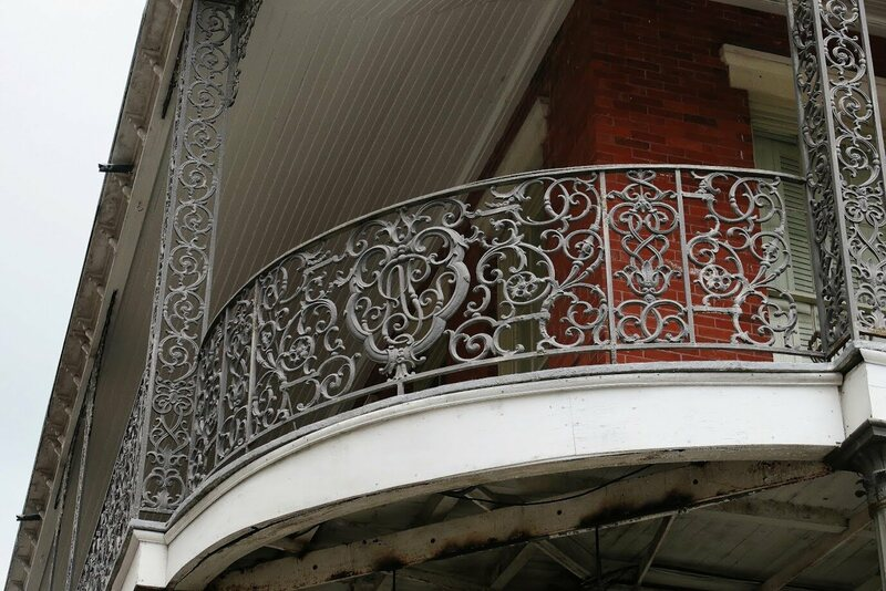 """The uninterrupted balconies of the Pontalba Buildings feature the initials """"AP"""" and an Adinkra symbol that means """"that which cannot be burned."""""""