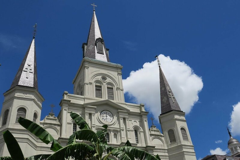 The left and right steeples of St. Louis Cathedral are topped with Adinkra symbols.