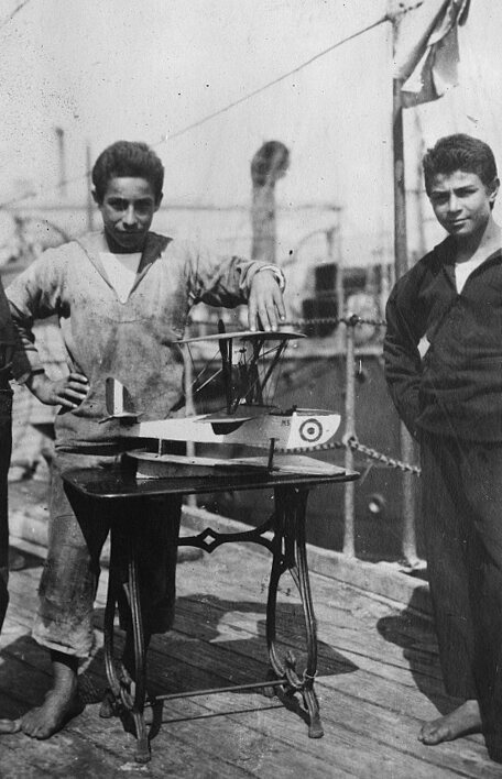 """One of the boys with an airplane he built. The caption in the American Red Cross archive states, """"He has a great talent for this sort of thing and could do really fine work if he [had] better tools."""""""