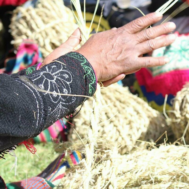 A Quechua woman braiding together blades of ichu grass during the festival.