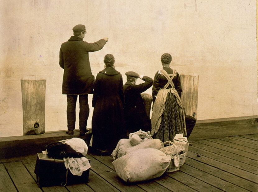 Four immigrants and their belongings, on a dock, looking out over the water at Ellis Island, 1912.