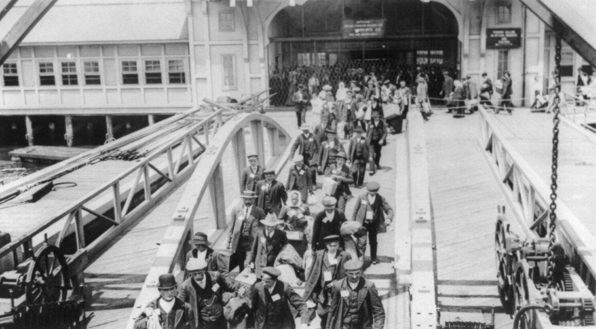 Immigrants walking across the pier at Ellis Island, early 20th century.
