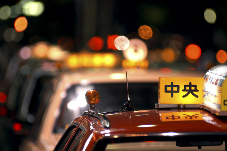 The brightly colored rooftops of Tokyo's taxi signs illuminates city streets.