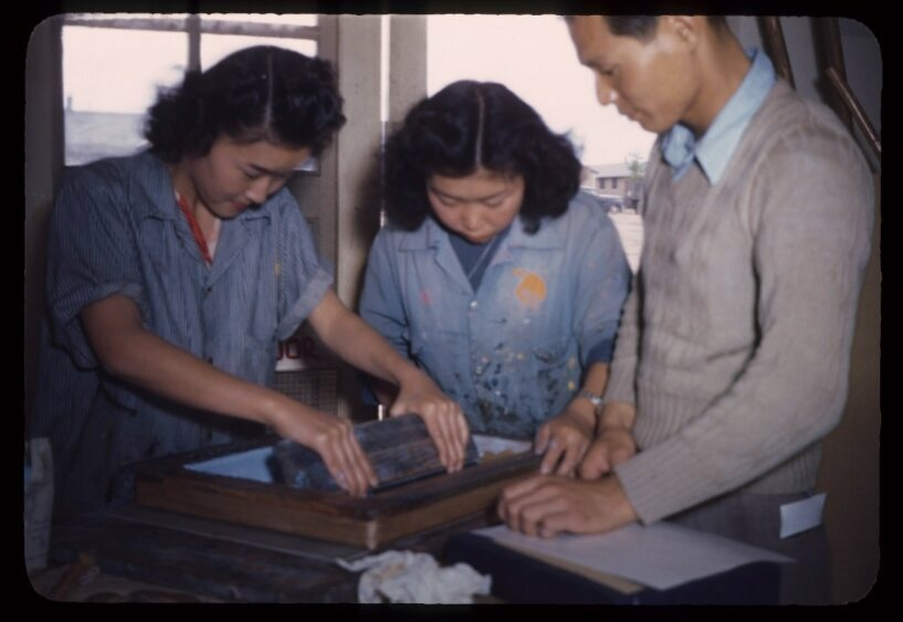 Three shop workers squeegee a print.
