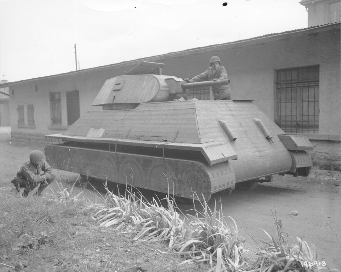 Two U.S. soldiers examine a fake German tank made out of wood. It was built on top of a German four-ton truck.