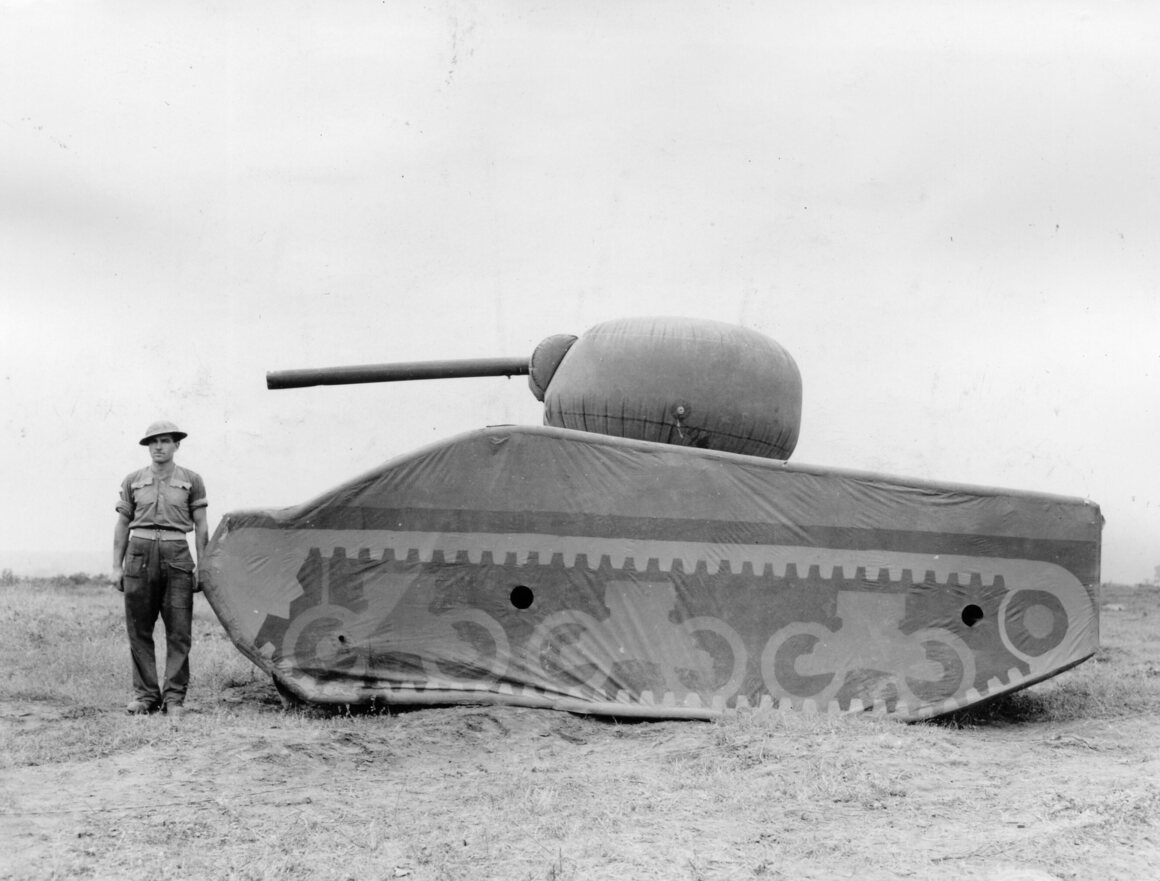 A soldier stands next to an inflated dummy tank made of rubber.