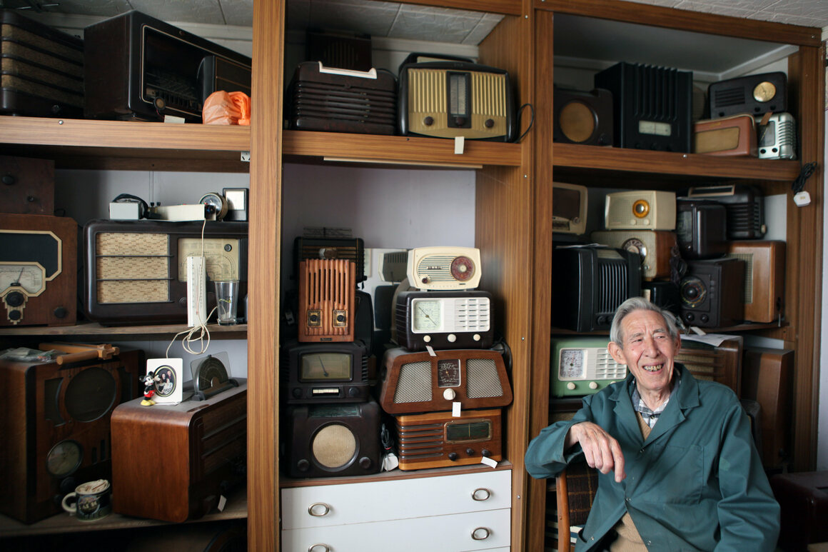 Ted Carter in one of the two bedrooms of his prefab, in front of his radios collection.