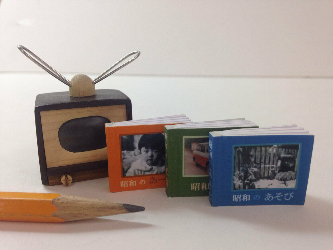 """Three miniature books about Japanese children in the 1930s and 1940s. The books fit into a television-shaped slipcase so their covers fill the """"screen,"""" by Akiko Noguchi, 2013"""