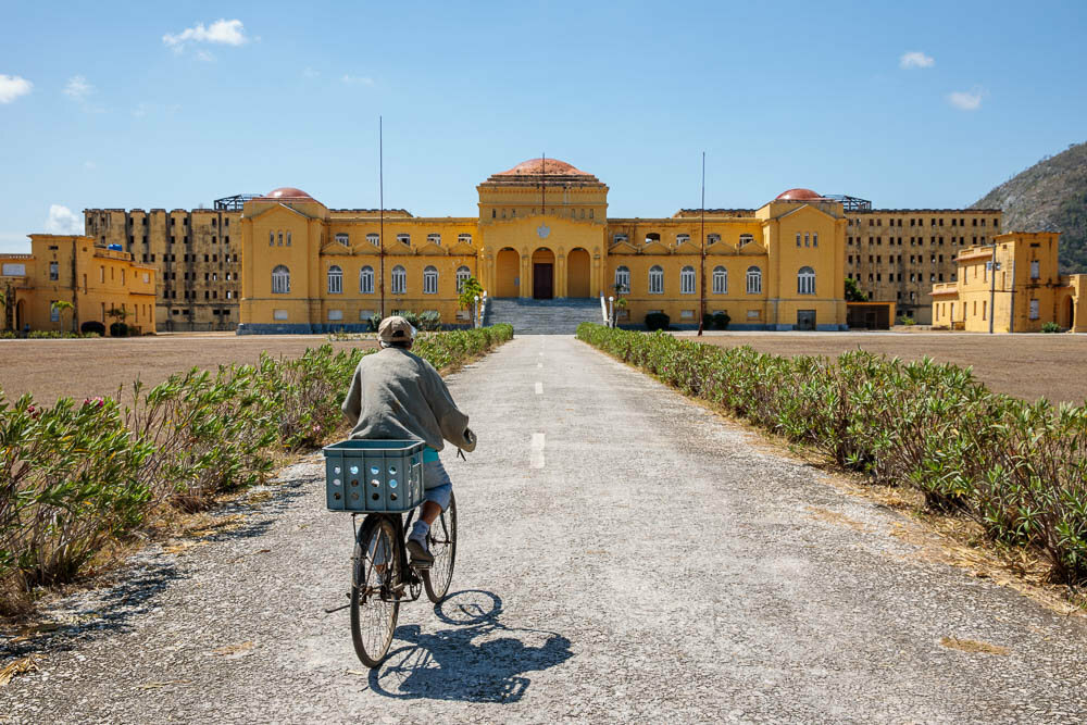 A local resident rides his bicycle through the entrance of Presidio Modelo.
