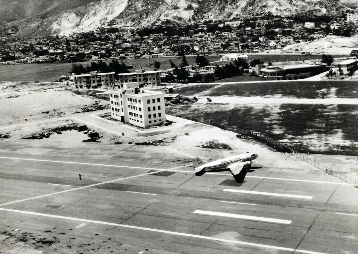 Cathay Pacific Airways Douglas DC-3 outside the airlines headquarters and stores building, Kai Tak Airport, 1959.