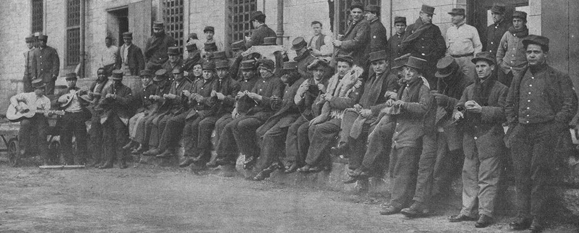 Prisoners knit in the yard at Sing Sing while listening to a concert by the mandolin club, 1915.