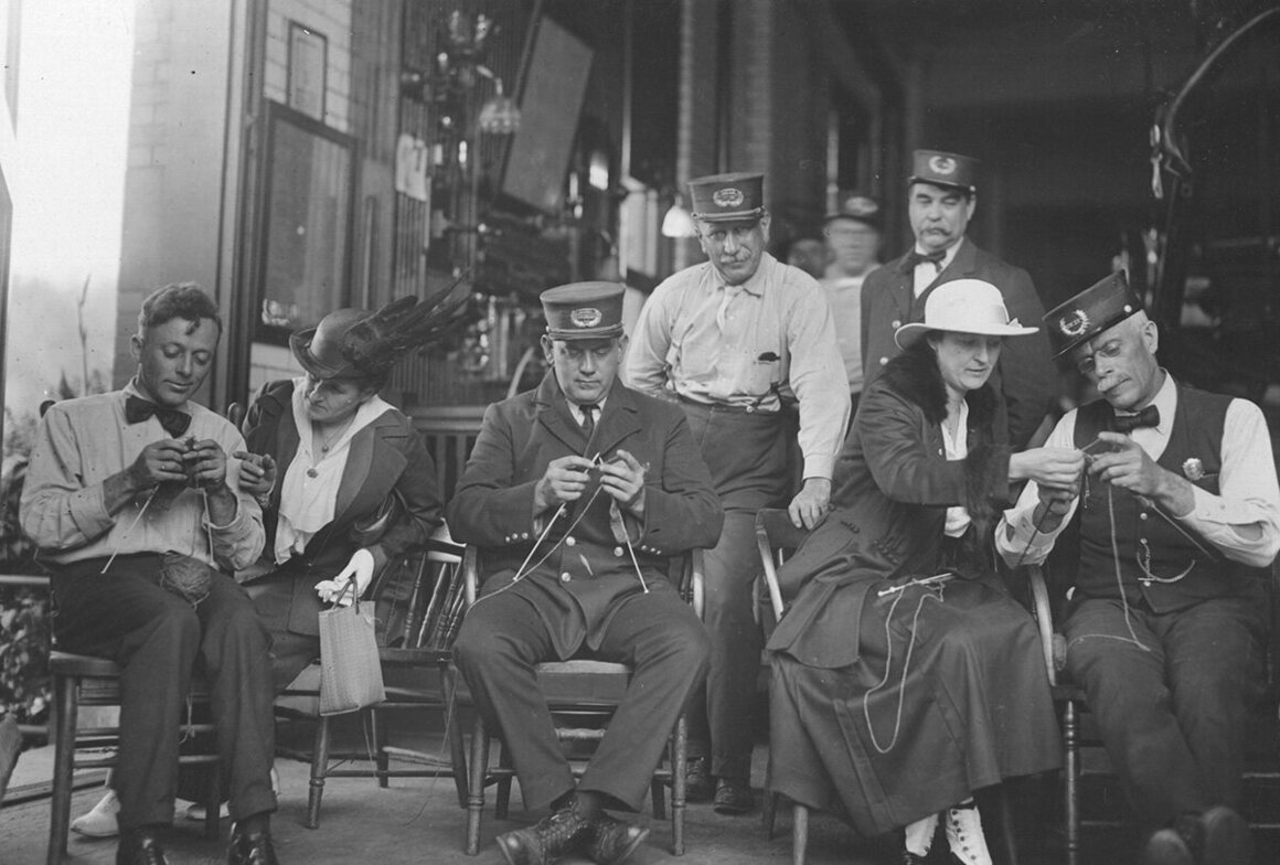 Firemen with the Cincinnati Fire Department being taught to knit by members of the American Red Cross, 1918.