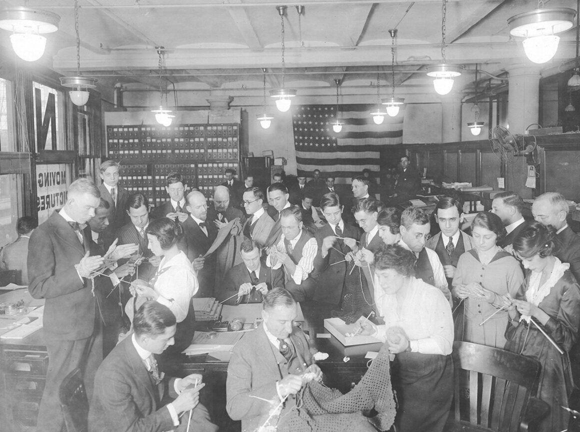 Male employees of the Universal Motion Picture Company knit during lunch hour, under the guidance of female stenographers.