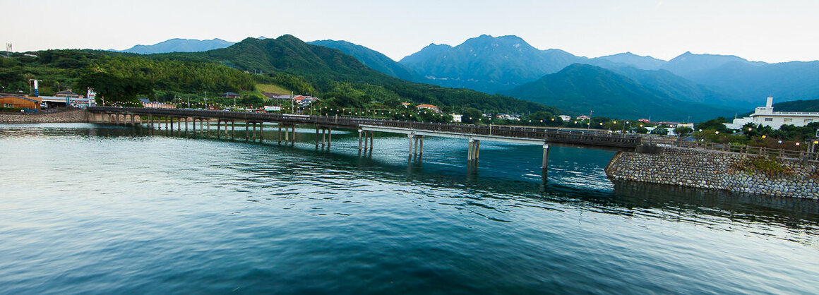 The undulating mountains at the center of the island serve as the backdrop for an archetypal Japanese lantern-covered wooden bridge at Miyanoura Port.